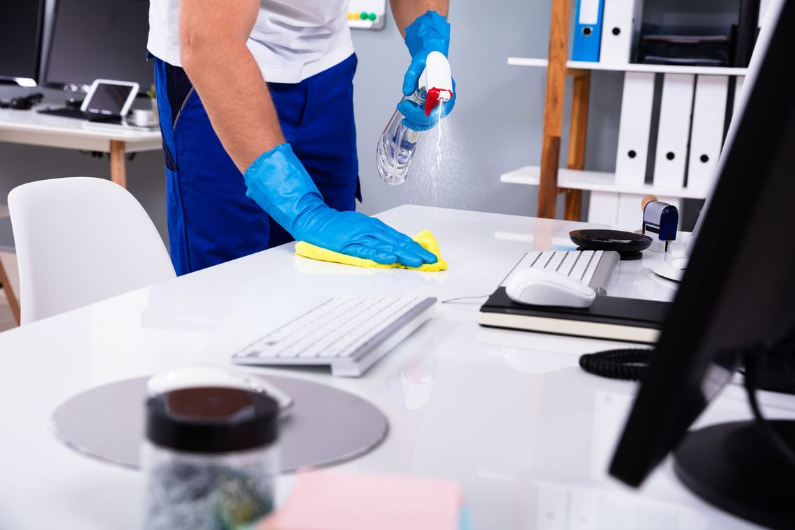 Objekt Perfekt in Hannover, Janitor cleaning white desk in office